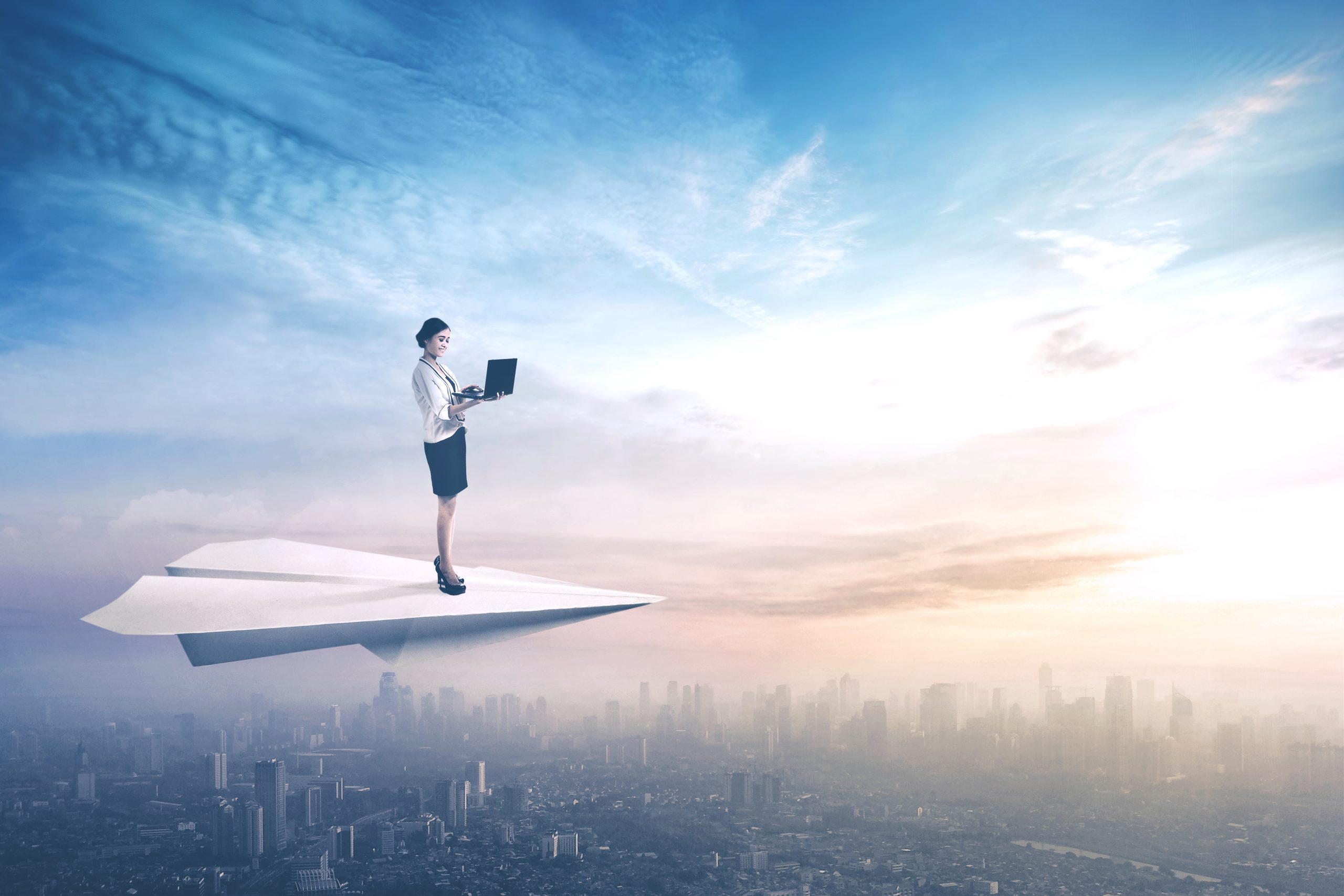 Businesswoman uses laptop on paper aeroplane