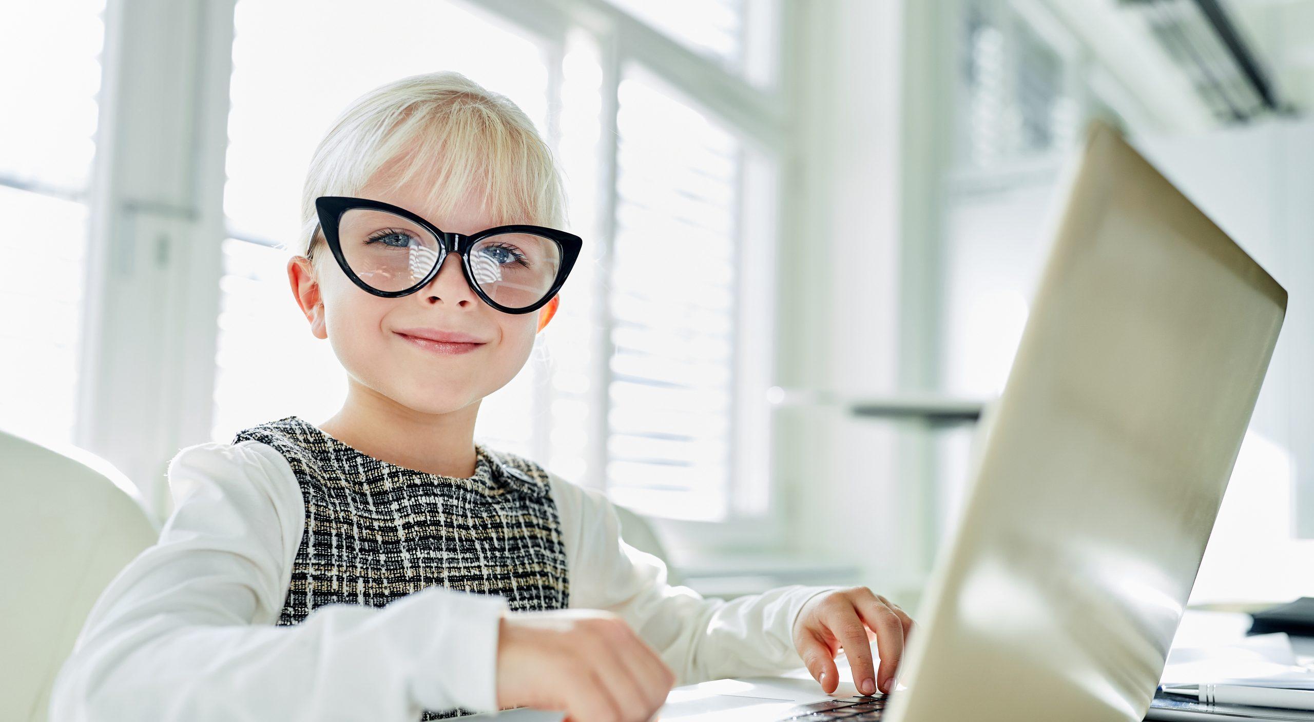 Lächelndes Mädchen sitzt als Geschäftsfrau vor Laptop Computer im Büro
